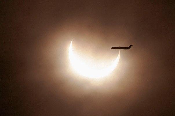 Самолет пролетает мимо солнечного диска во время затмения