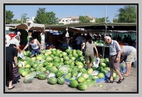 Старик продаёт на базаре арбузы под табличкой